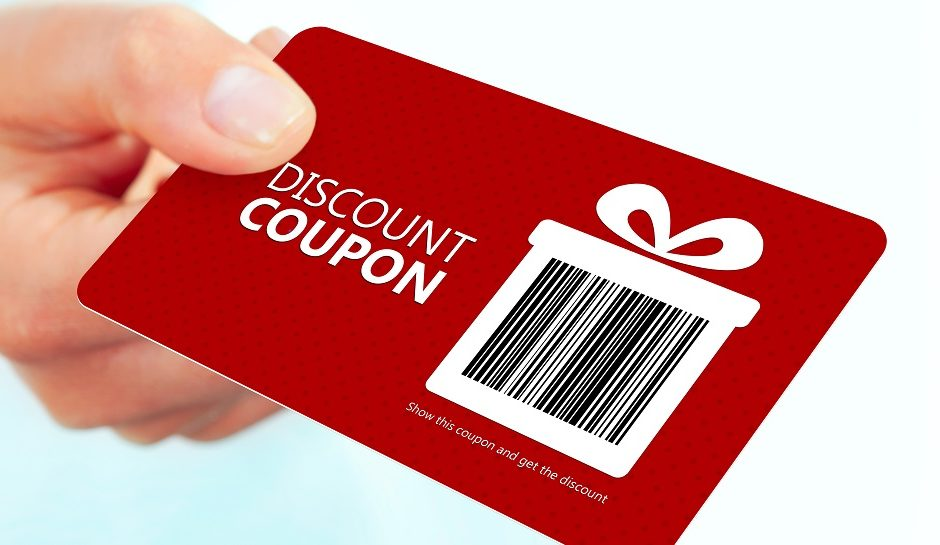 red christmas coupon holded by hand over white