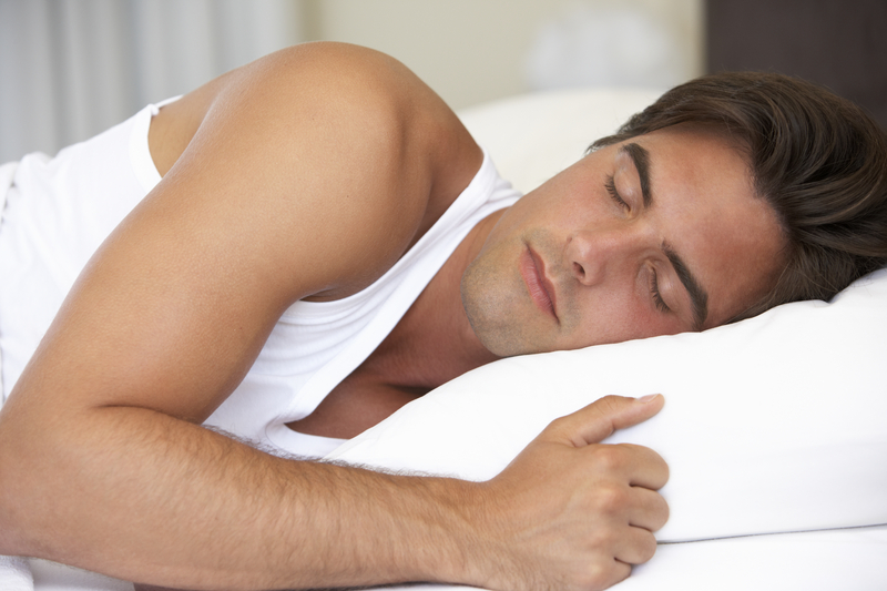 Young Man Sleeping On Bed